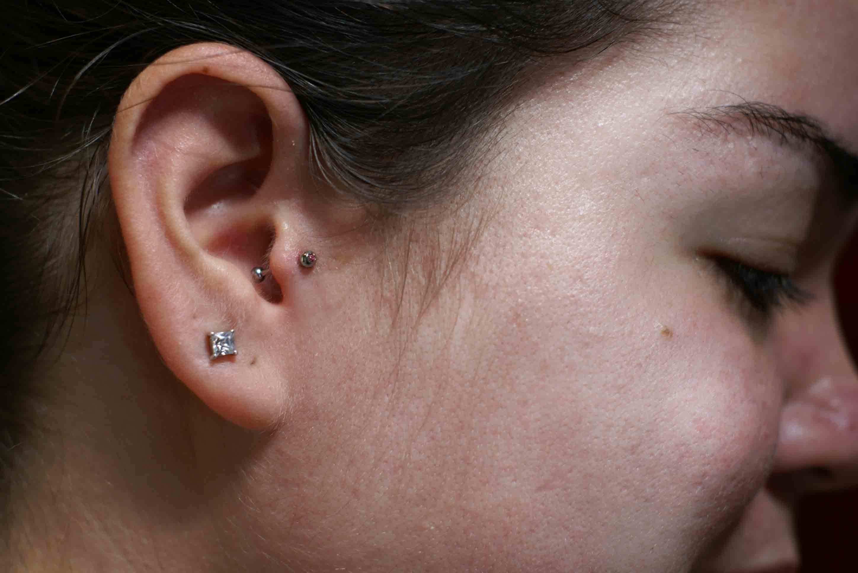 The pericing between the cheek and the tragus looks like a ...